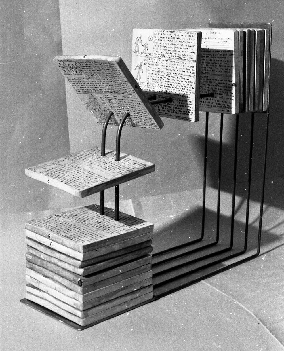 The wooden handwritten/ -drawn pages are threaded through holes on metal tubes which form a cube