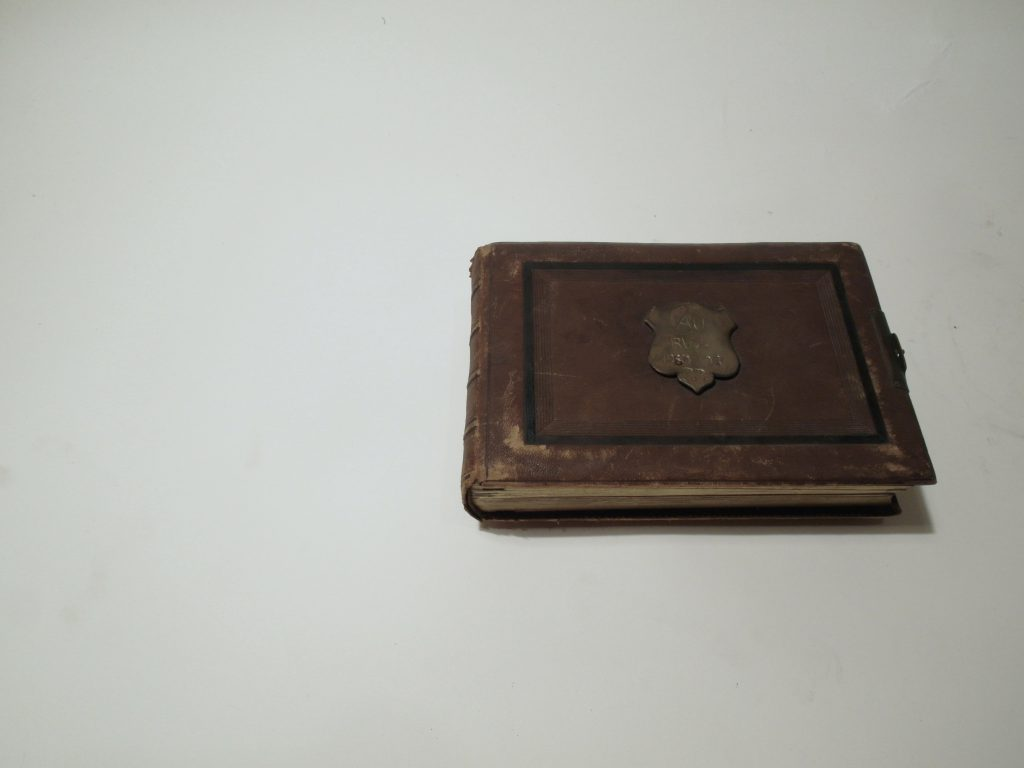 Book with worn out leather cover and metal emblem in the center.