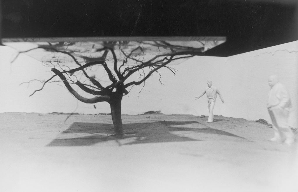 An upside down tree stucks in the ground. Figures around.
