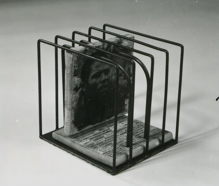 Tubes bent on form of a cube fixed on a base plate. Wooden panels threaded through holes on one side on the tubes.