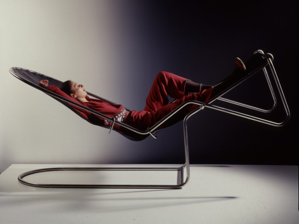 Woman relaxing in a deckchair made from metal tubes and a black leather lying-area.