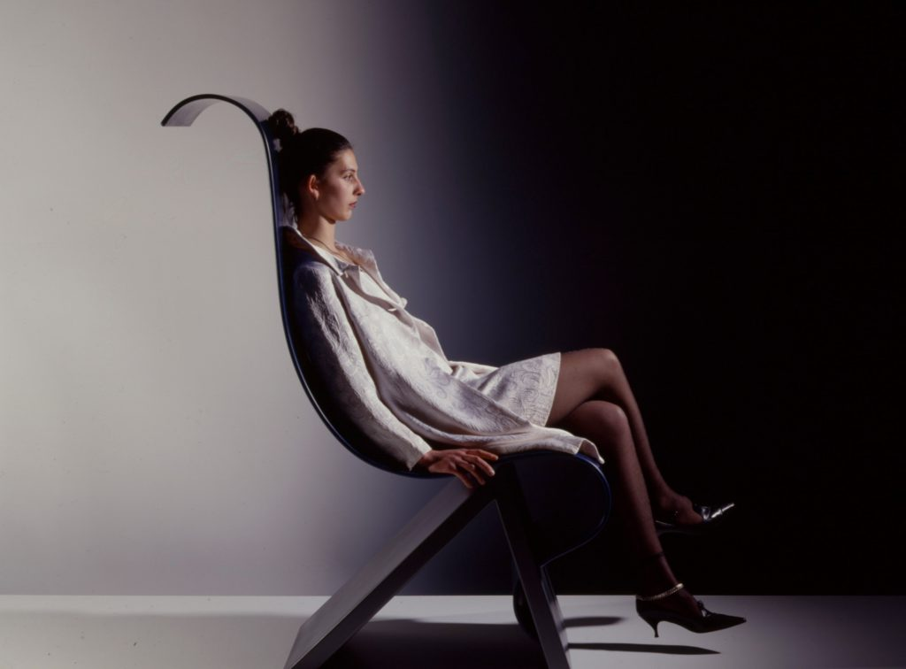 Woman is sitting on wave-formed chair.