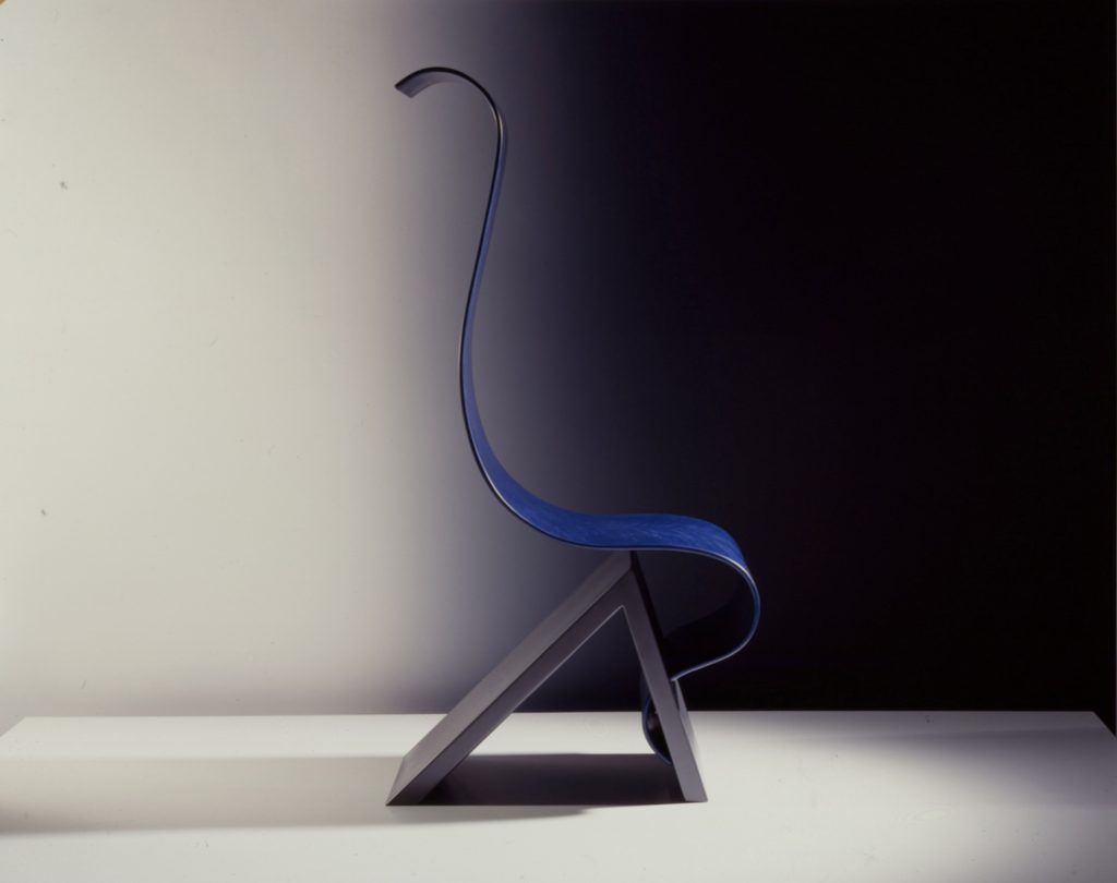 Chair consists of wave-formed sitting area mounted on the edge of a triangular base.