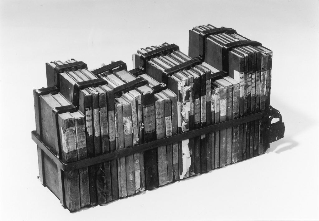 Row of books ordered by size. Entire row packed into a metal frame locked with a padlock.