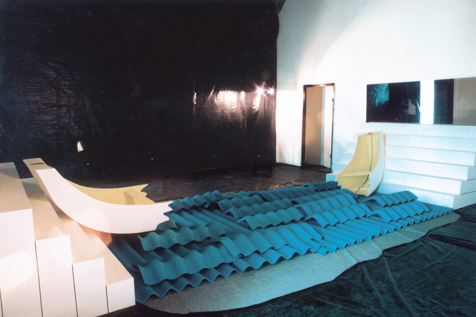 Floor and one wall of a white room covered with black plastic foil. Blue corrugated panels stretch between 2 podests in the center. Each half of a shipwreck leans against the podests.
