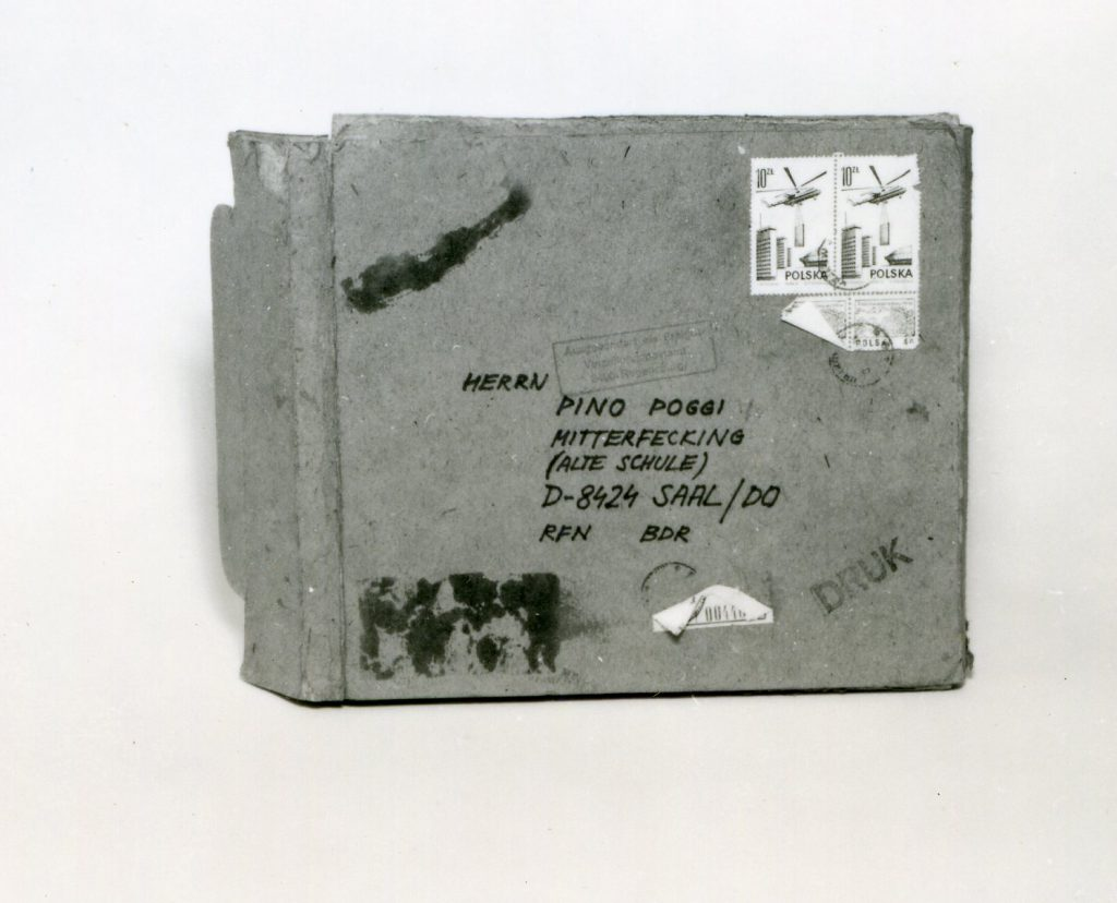 Small cardboard briefcase with handwritten adress and stamps.