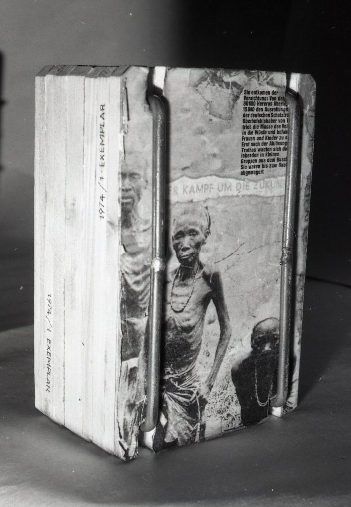Magazine pages of malnourished people collaged onto wood panel.