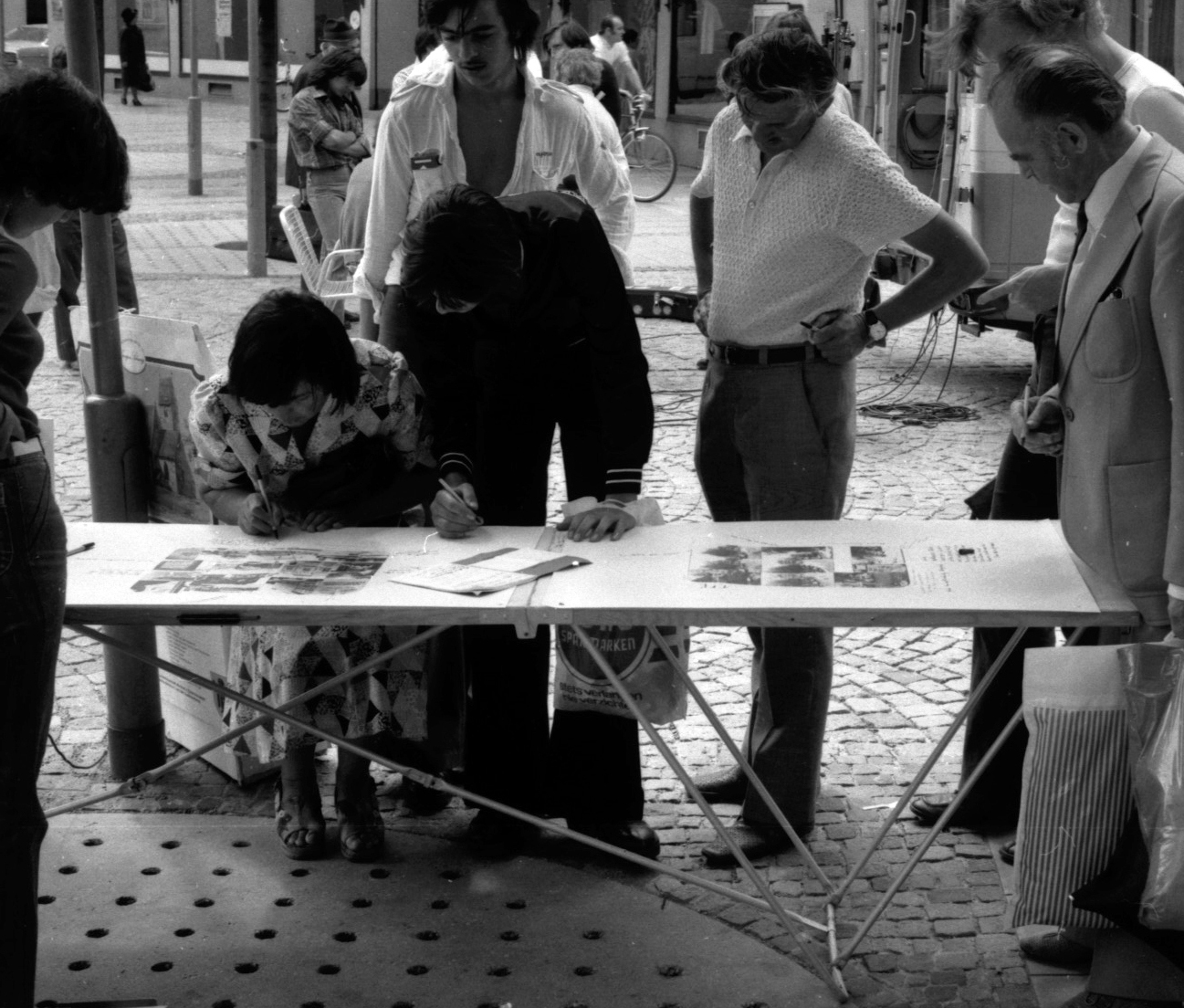 A table with graphic material standing in the street. 2 persons writing on some sheets. Other persons standing around and watching them.
