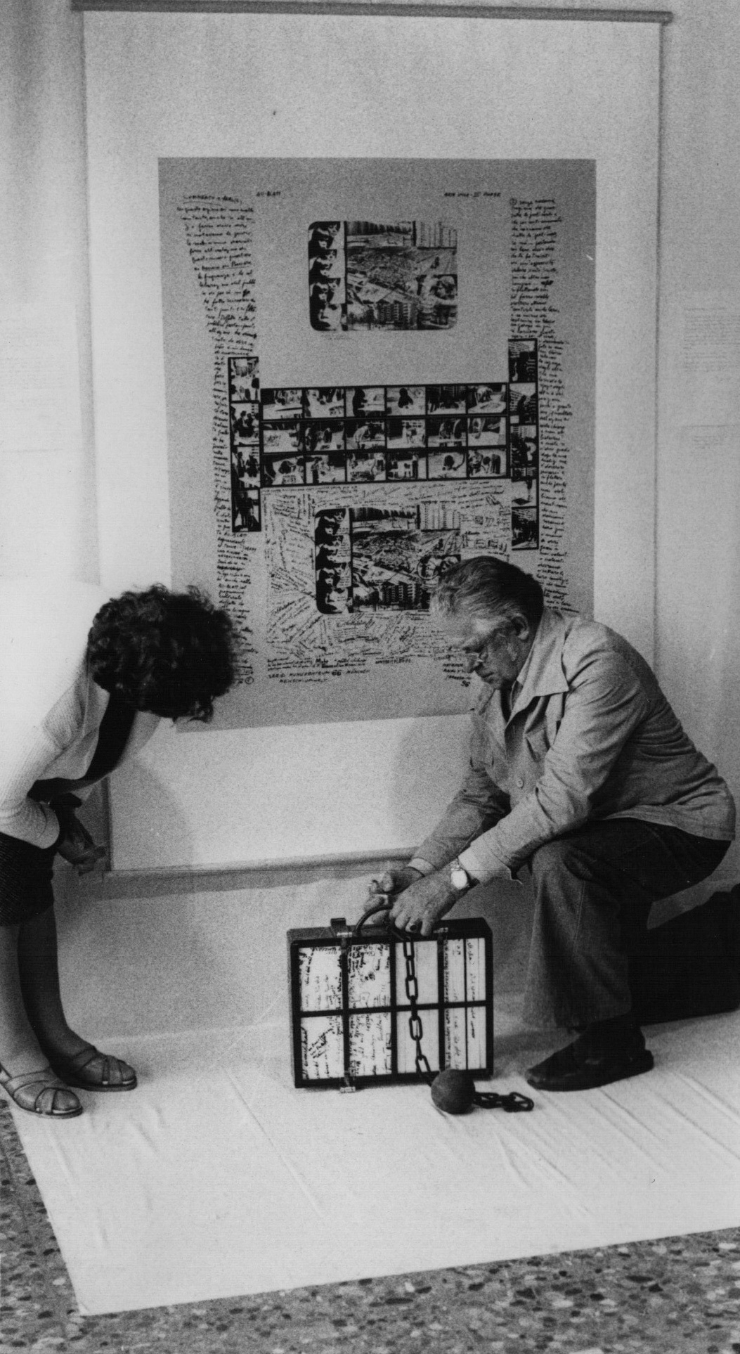 A white cloth covers partly a wall and also stretches over the floor. On the wall hanngs a large sheet with several collages and lots of handwritten text. Two persons standing on the white cloth.
