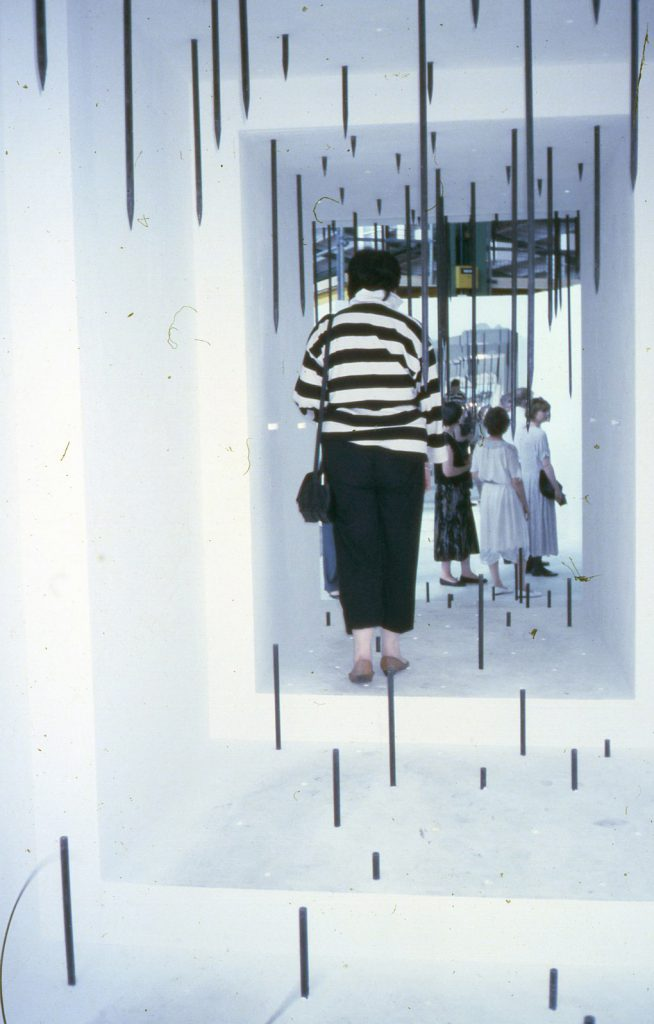 People walking through a cuboid tunnel. Sharp metal bars rise up from floor and down from ceiling.
