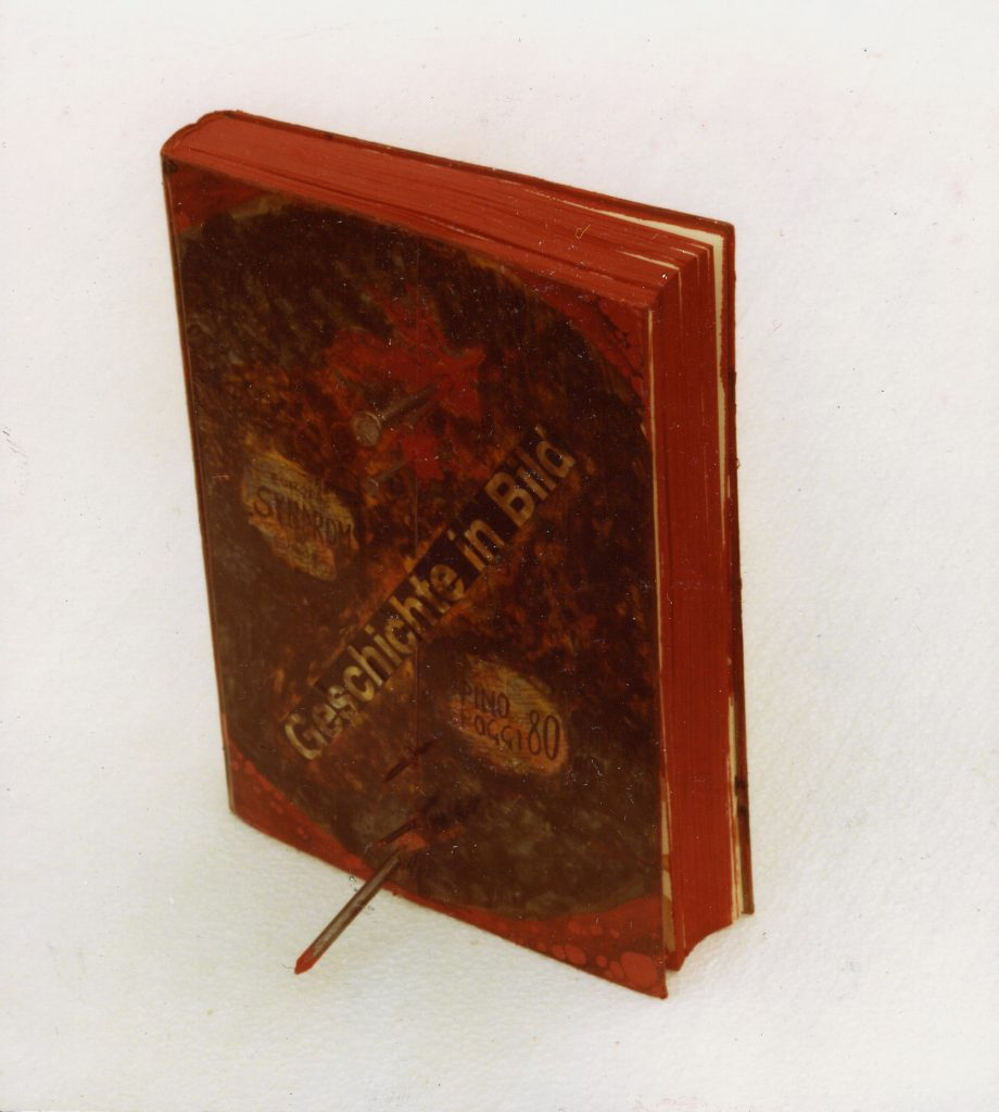 Book with red paint all over. Several nails penetrate the book body.