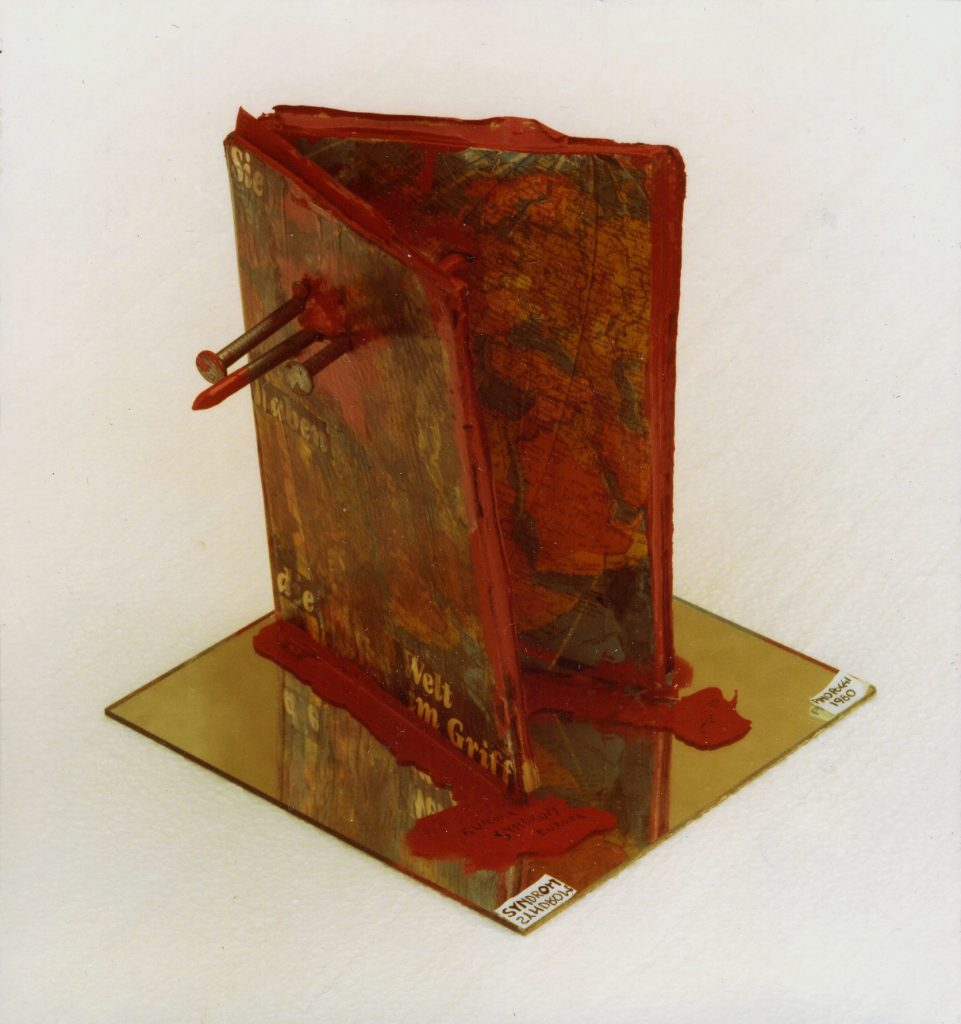 Partly opened book soaked in red paint mounted on a mirror. Large nails penetrate the book body.
