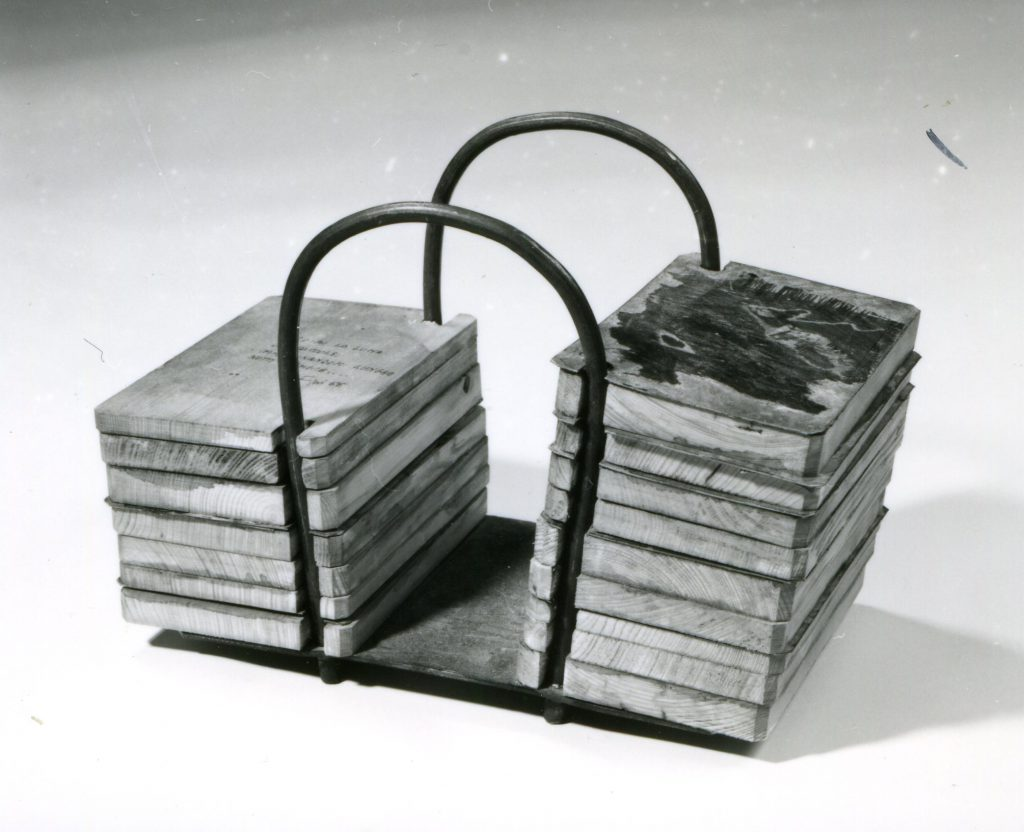 A construction of 2 bended metal tubes on a base plate. Wooden panels threaded through holes on the metal tubes.