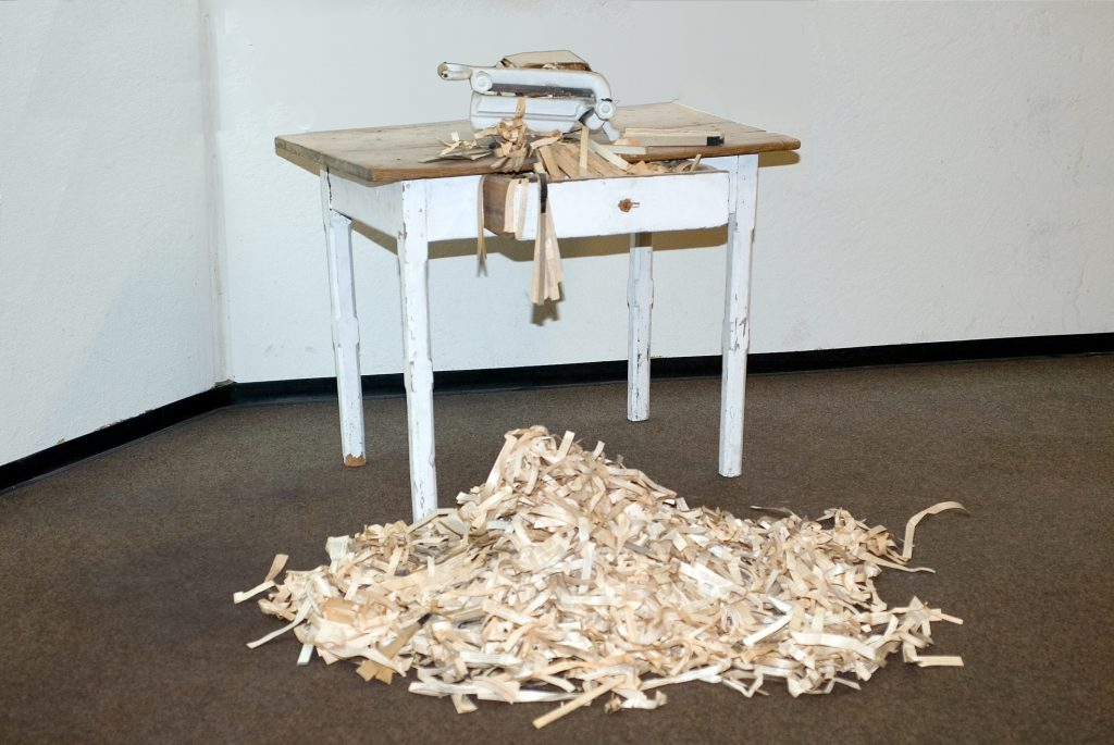 Small wooden table with a manual bread slicer. Lots of paper scraps on the floor.