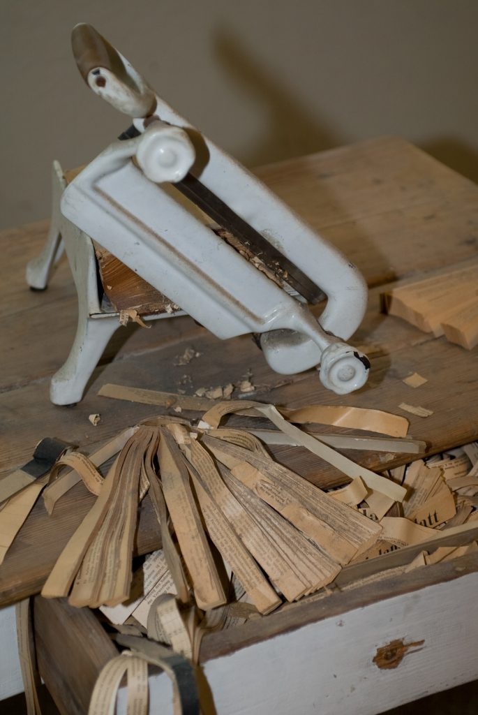 Manual bread slicer with a pack of half cutted books and paper scraps around.