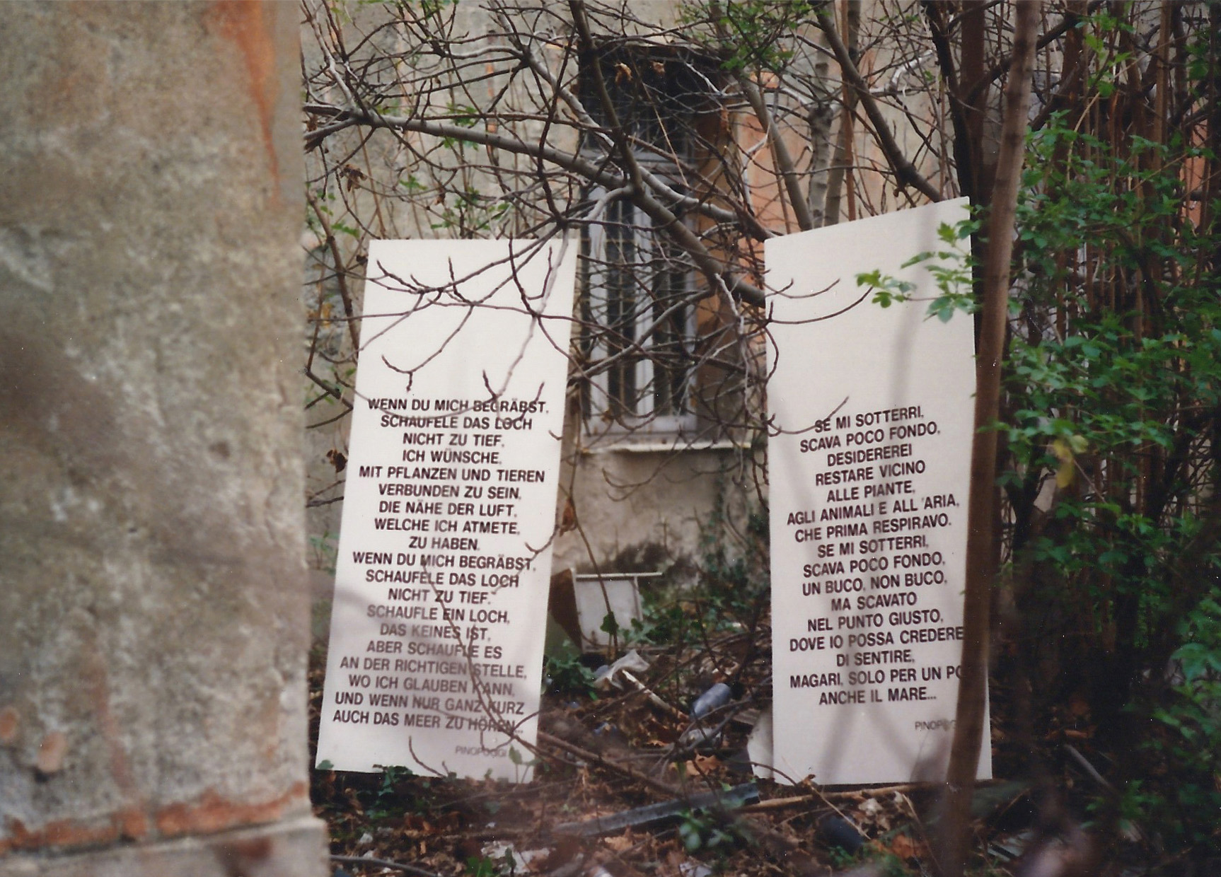 2 white boards with black text in german and italian standing in a shabby backyard.