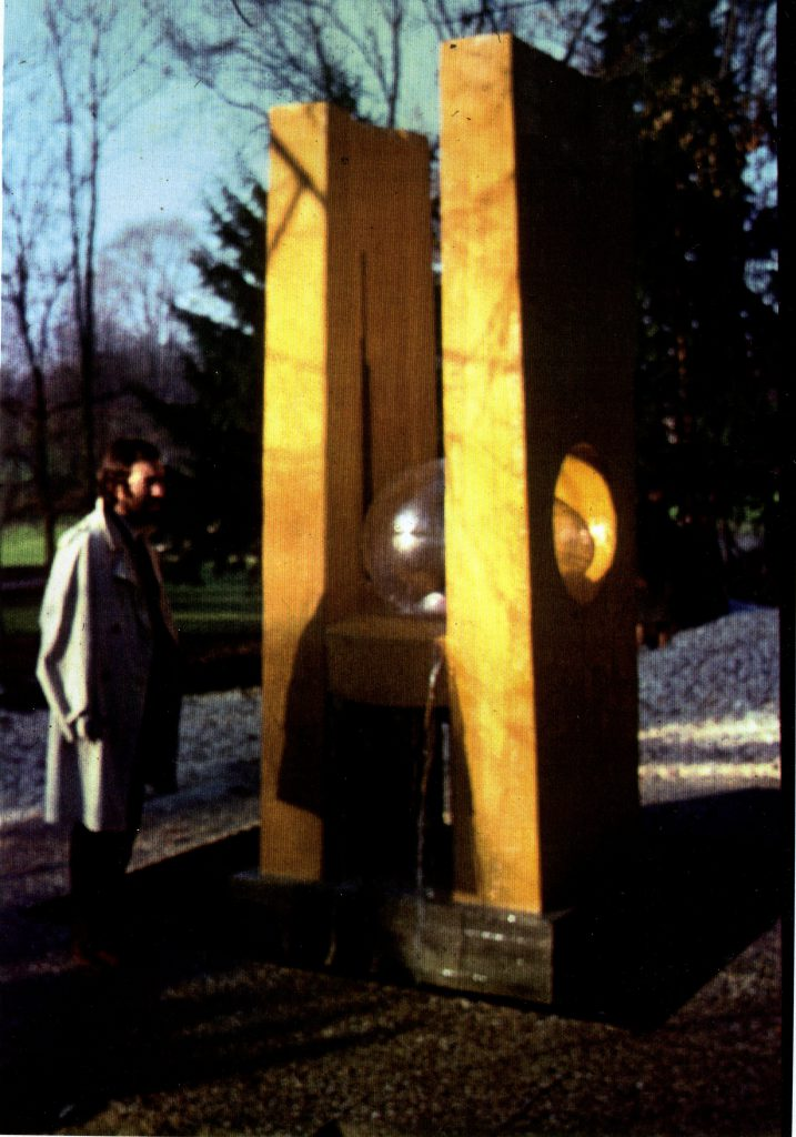 Man standing beside a fountain sculture in shape of letter H. On crossbeam of H a transparent ball is mounted. Water runs down underneath.