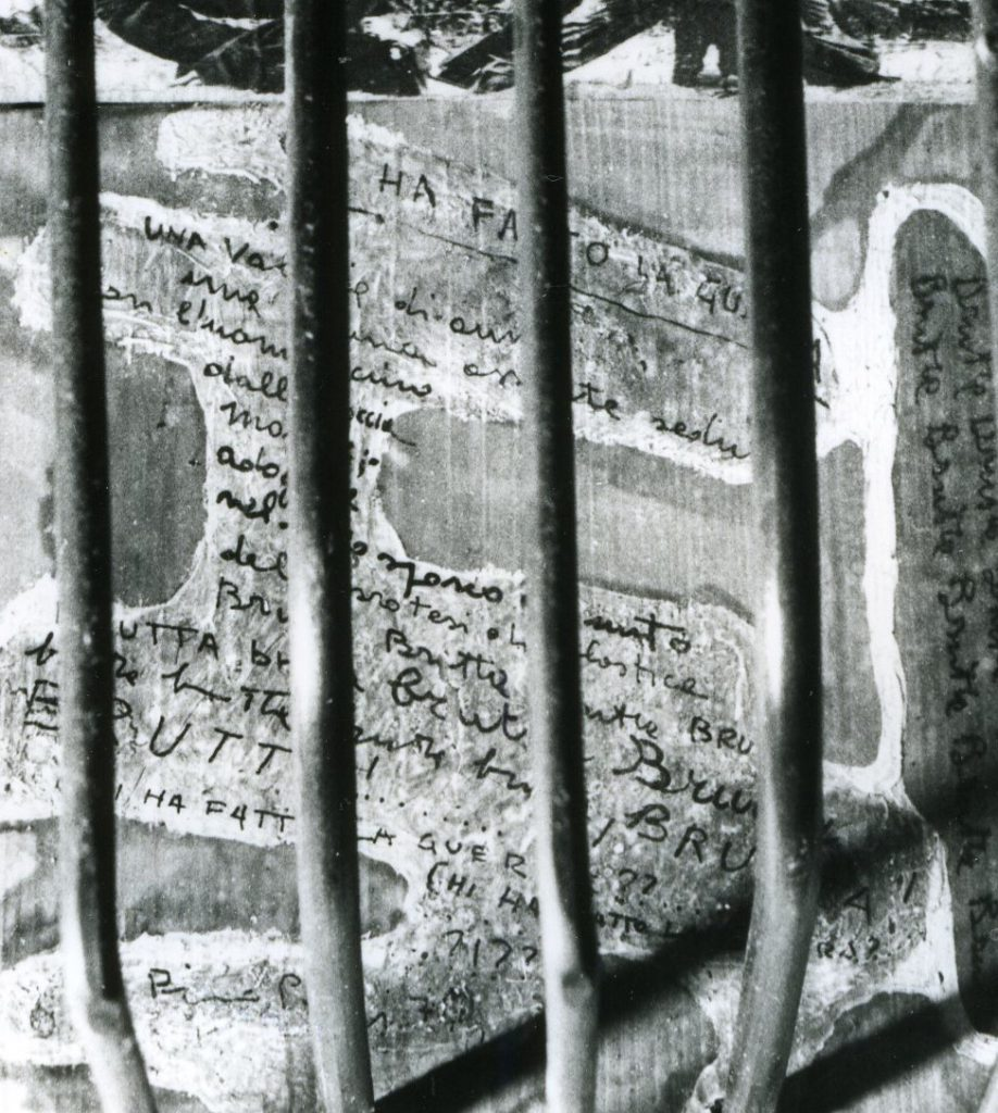 Wooden panels with handwritten text behind metal tubes.