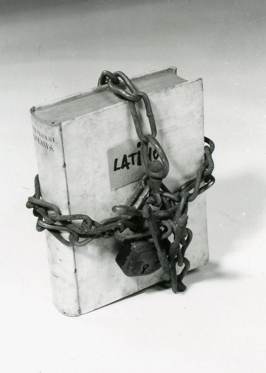 """A found book wrapped with iron chain closed by padlock. A sticker with the handwritten word """"Latino"""" covers the original title."""