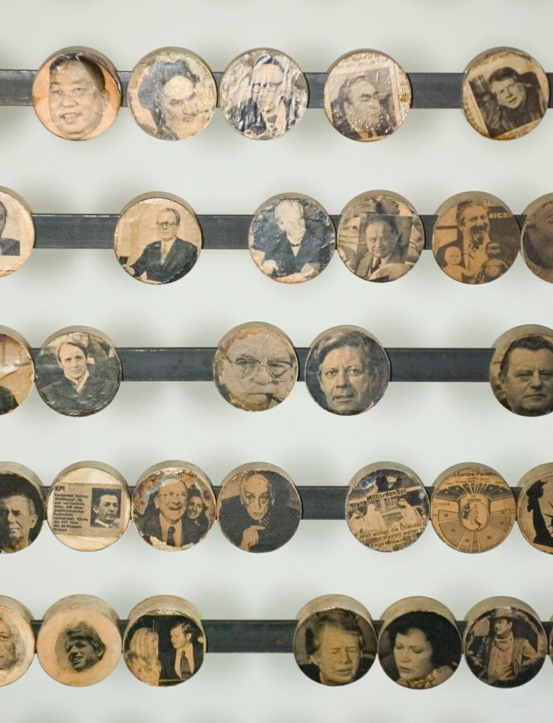 A sliding ruler. Portrait photos of important personalities are collaged onto the sliding discs.
