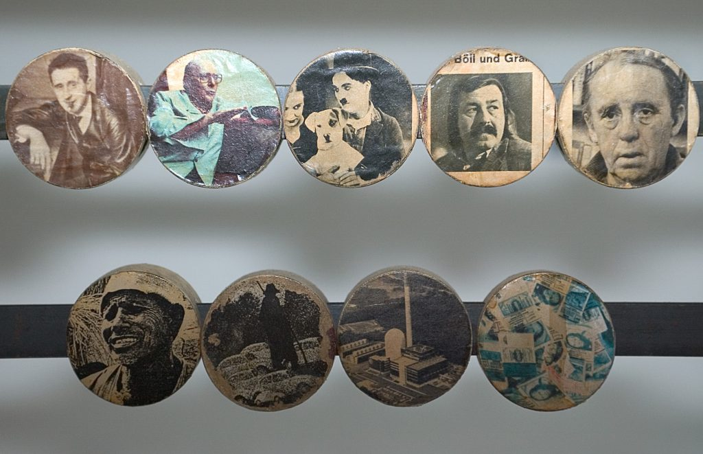 Portrait photos of important personalities are collaged onto the sliding discs.