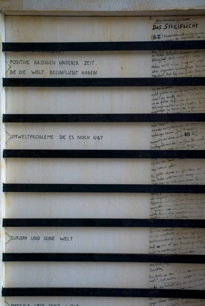 Panel behind sliding ruler: Handwritten texts working as a key to the sliding ruler.