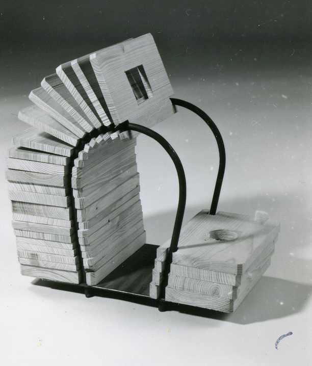 A conctruction of metal tubes with threaded wooden panels. A geometrical form is cutted out in the middle of each panel.
