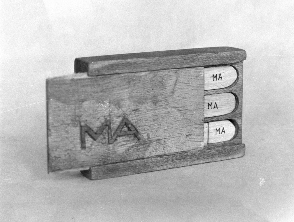 """Wooden casket with a sliding cover showing the letters """"MA""""."""