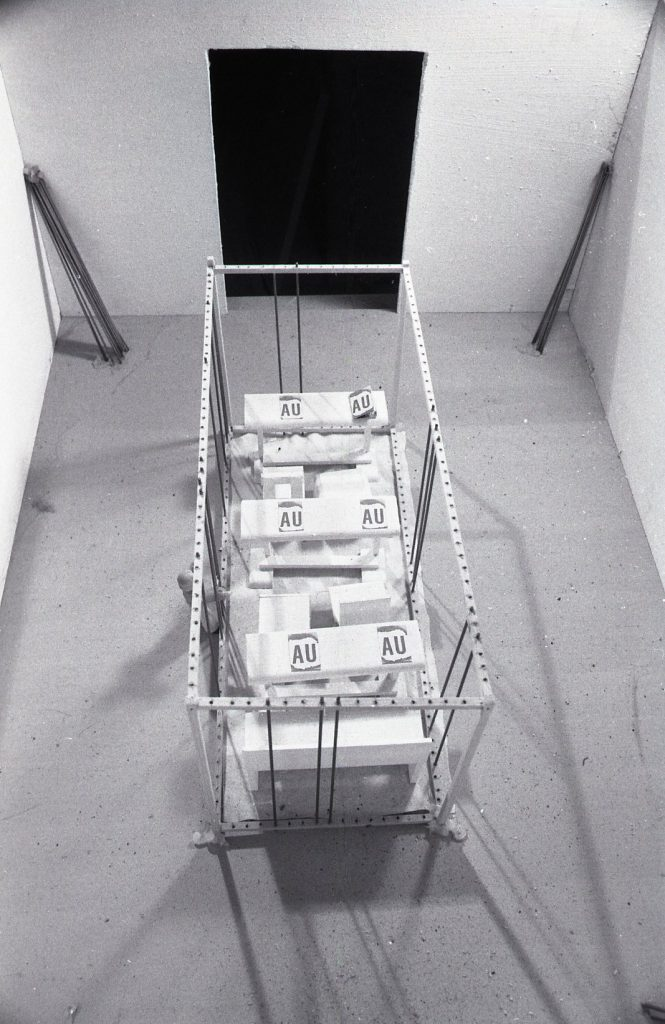 A cubic cage construction in a room. Desks with AU-sheets and chairs are placed inside the cage construction.
