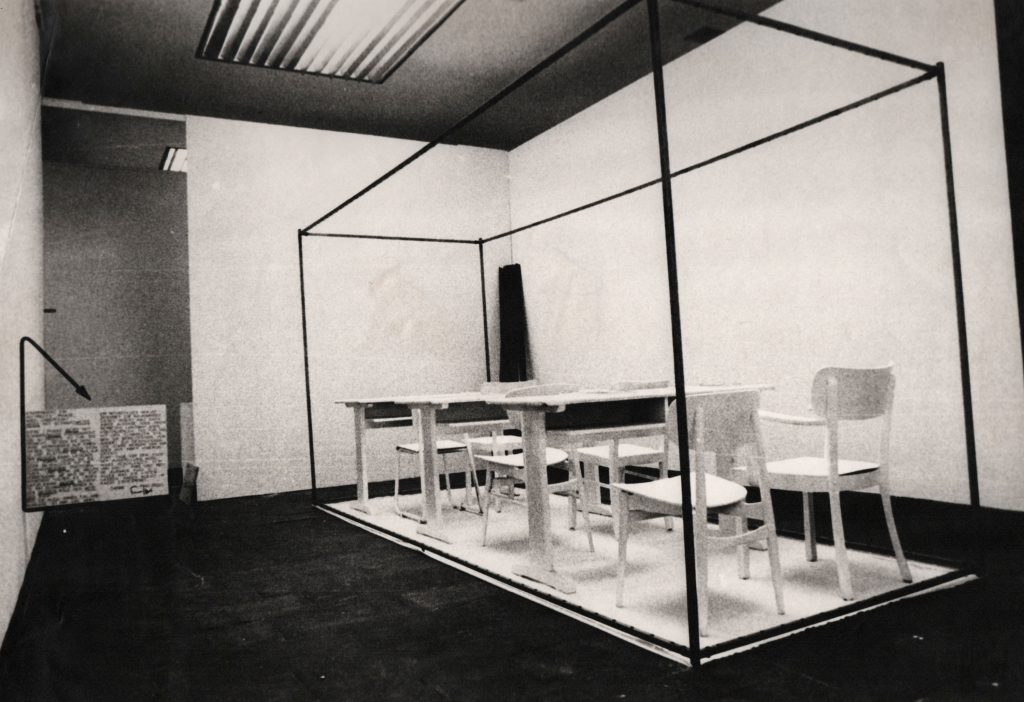 Inside a gallery room a huge white sheet lies on the floor. White school desks and chairs are placed on the sheet. A cubic construction of metal tubes bounds the space of the white sheet.