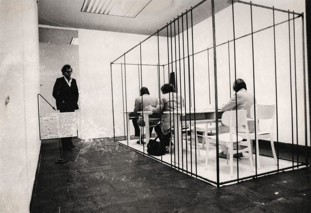 Some visitors sitting at the desks. More bars are added to metal construction becoming more and more a cage.