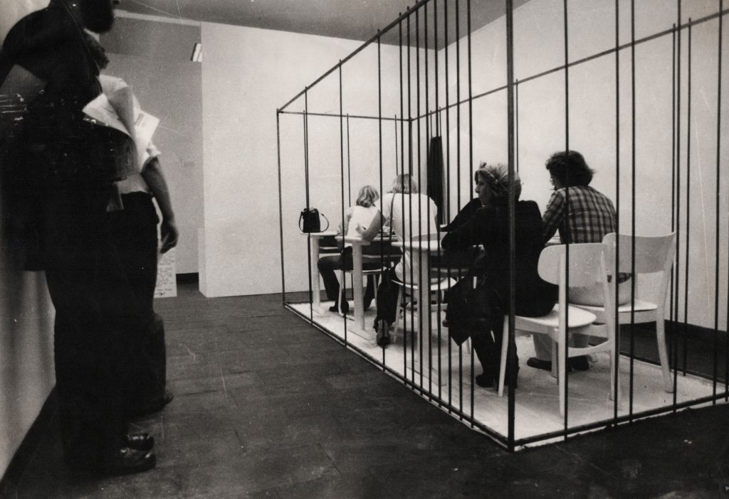 Visitors sitting at the desk and inside the developing cage.