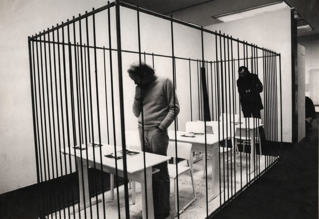 Visitors standing in front of the desks looking at the books. More bars are added to the construction. Only few spots left to enter the cage.