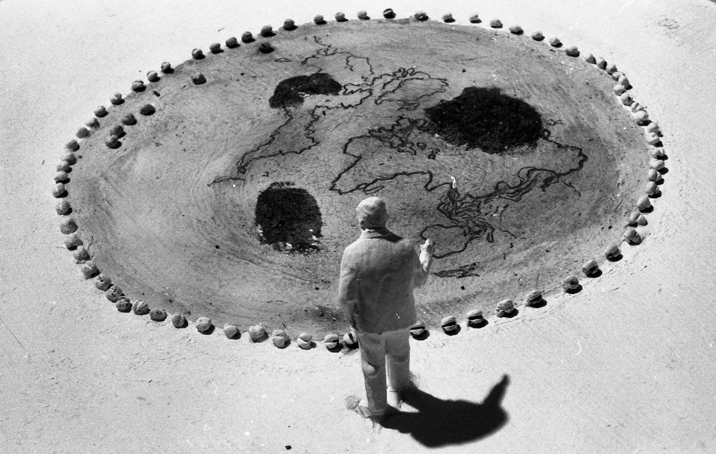 A figure stands beside a circle edged by small stones. A map of the world before the continental drift is drawn inside the circle.
