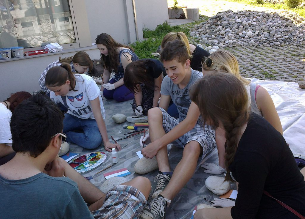 Youngstas sitting on the floor and painting stones.