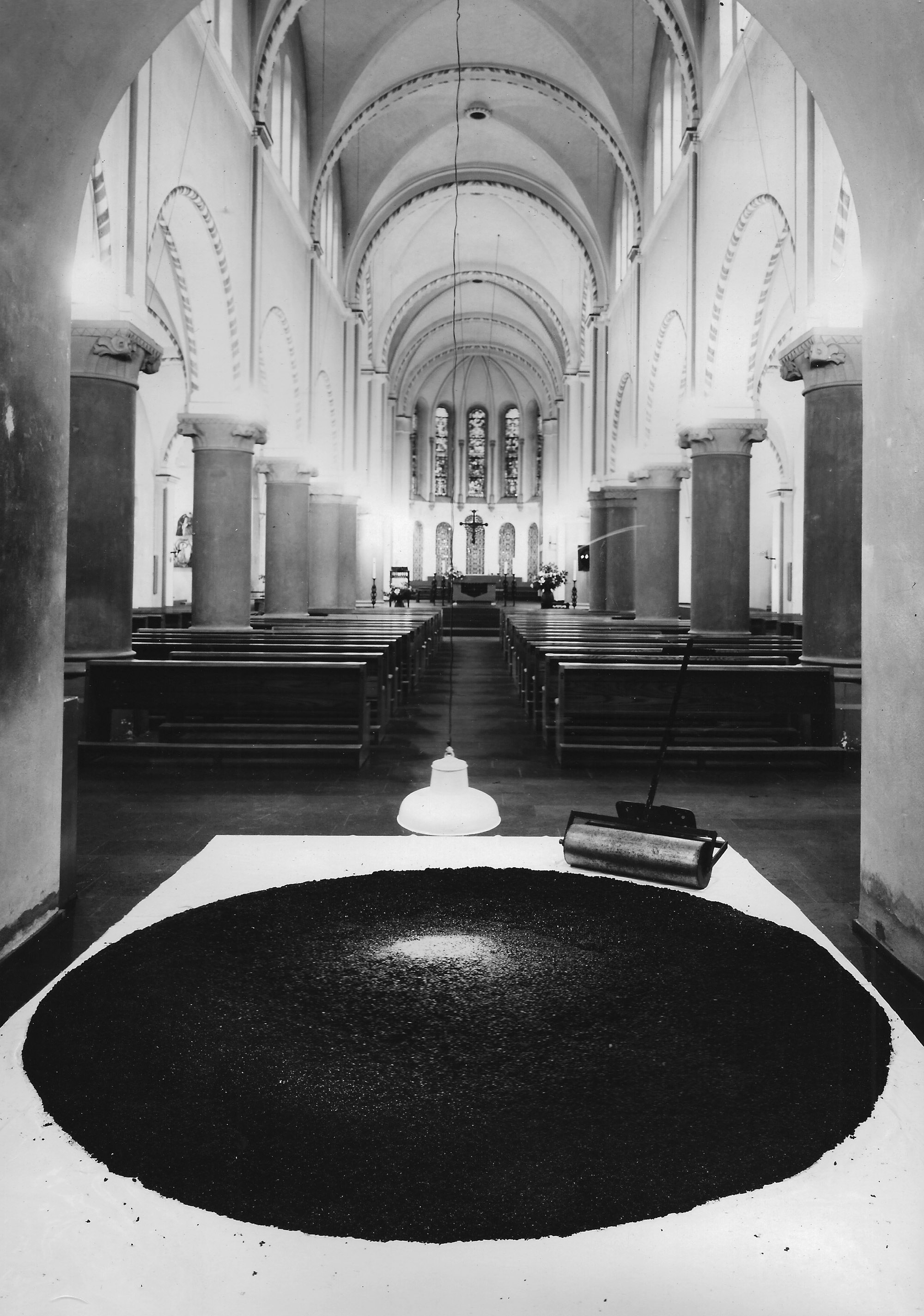A large circle of tar placed on a white sheet on the floor inside a church.