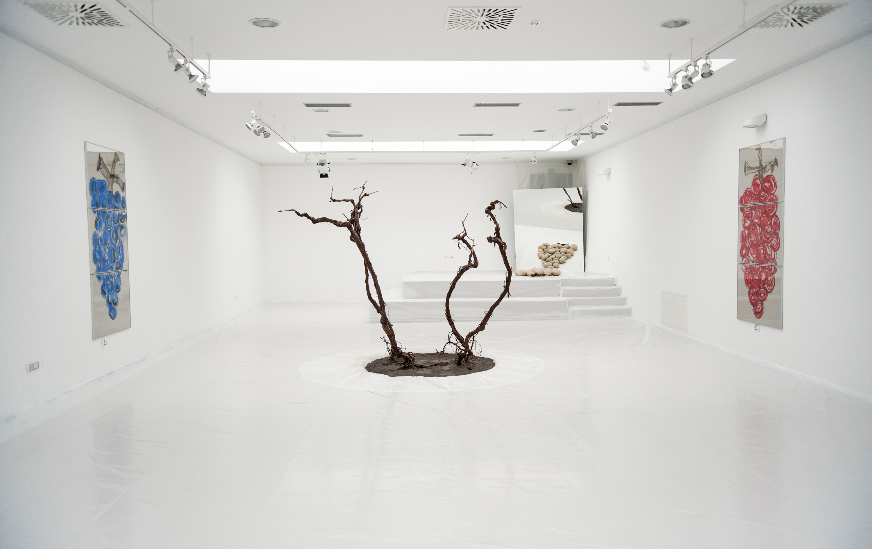White gallery room. Branches placed upright in the middle. On 2 opposite walls hang huge mirrors with a large grapevine drawings. A podest with stockpile of stones and a mirror in the back of the room.