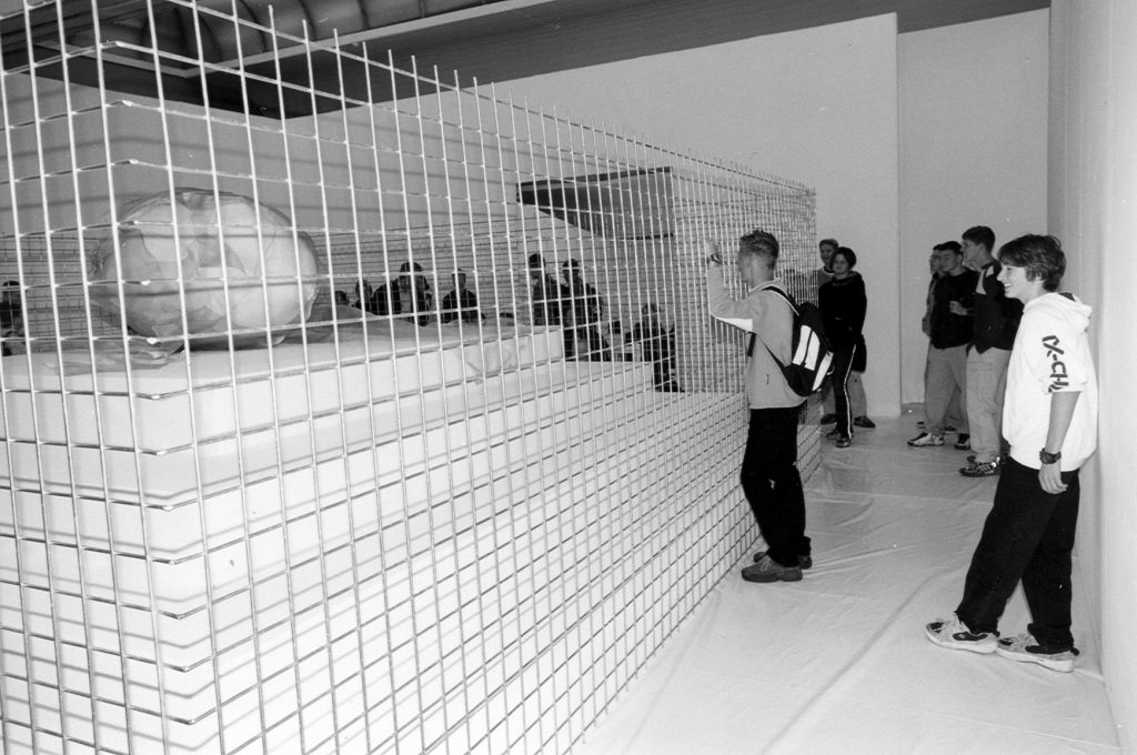 Gallery visitores in the room watching the Installation.