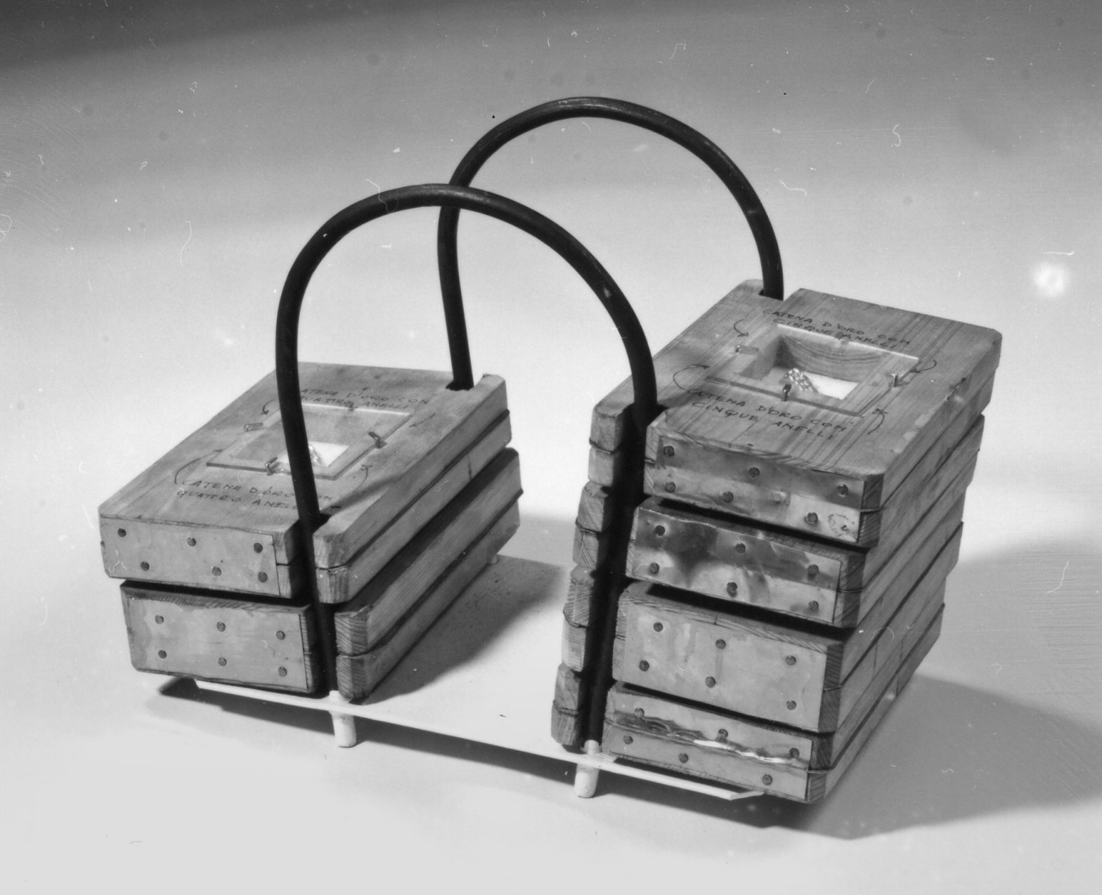 A conctruction of metal tubes with threaded wooden panels. Each wood panel has a square form cutted out in the middle. This holes're covered with glass and contain parts of a golden chain inside.