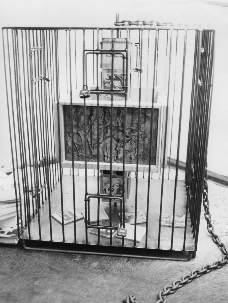 A metal cage with small doors locked by padlocks. The totem-like pole inside contains collaged photography and small wood reliefs.