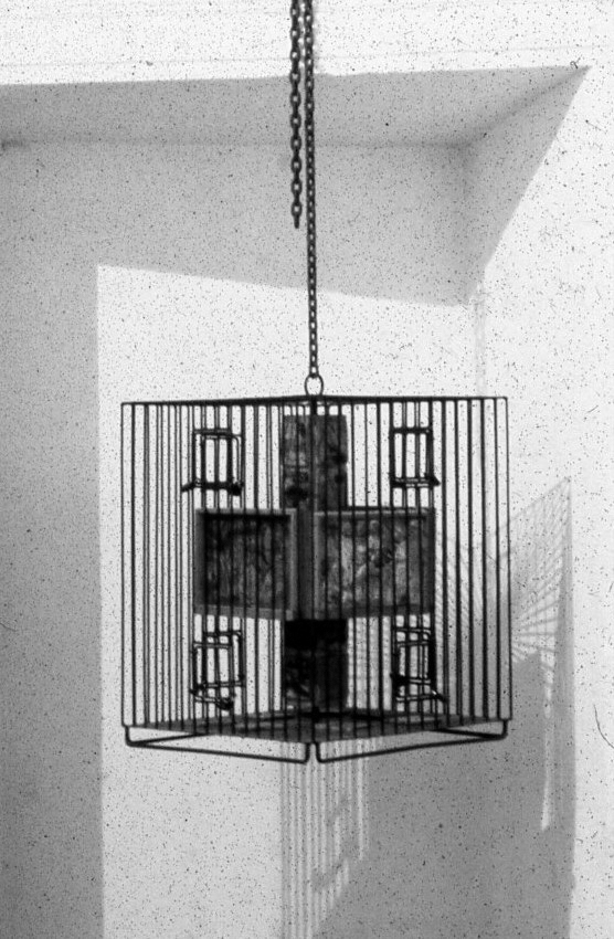 A metal cage hangs on a chain. Inside in the center of the cage a totem like pole with assembled small wodden panels.