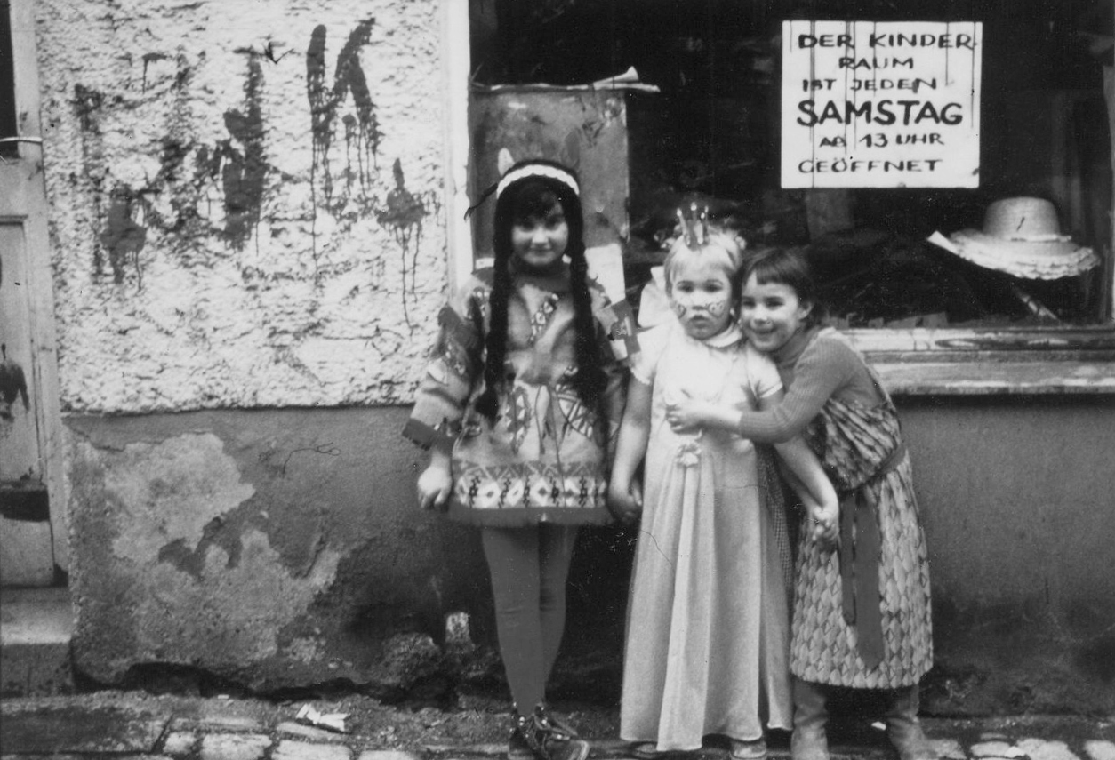 § kids in front of shopwindow next to entrance. Poster with handwritten note hangs inside window.