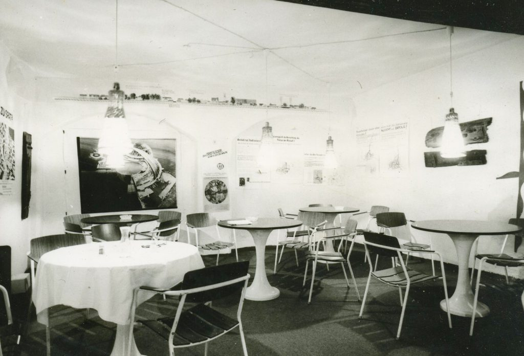 Cafeteria with several tables and Posters hanging on walls.