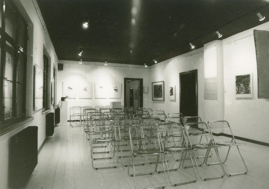 Empty room with rows of foldable chairs in the middle. Framed artworks hang on walls.
