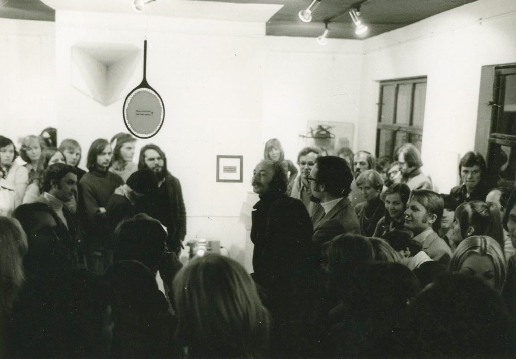 Man encircled by other peple. Holding a speech.