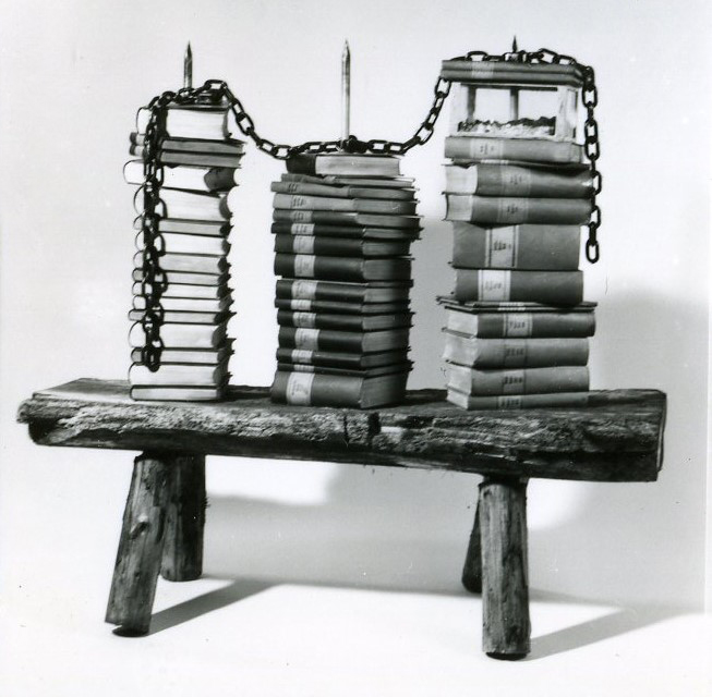 On a simple rustic wooden bench 3 piles of books pierced by a metal lance. A metal chain connects the lances at their top. One pile contains a glas casket in beteen the books.