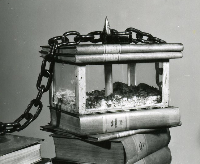 A glas casket containing scraps of book pages.
