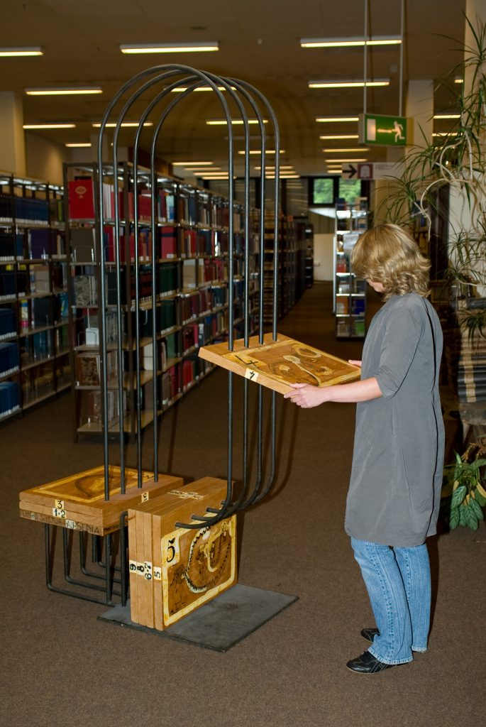A woman stands beside the chair construction. She holds one of the wooden panels in her hands and reads.
