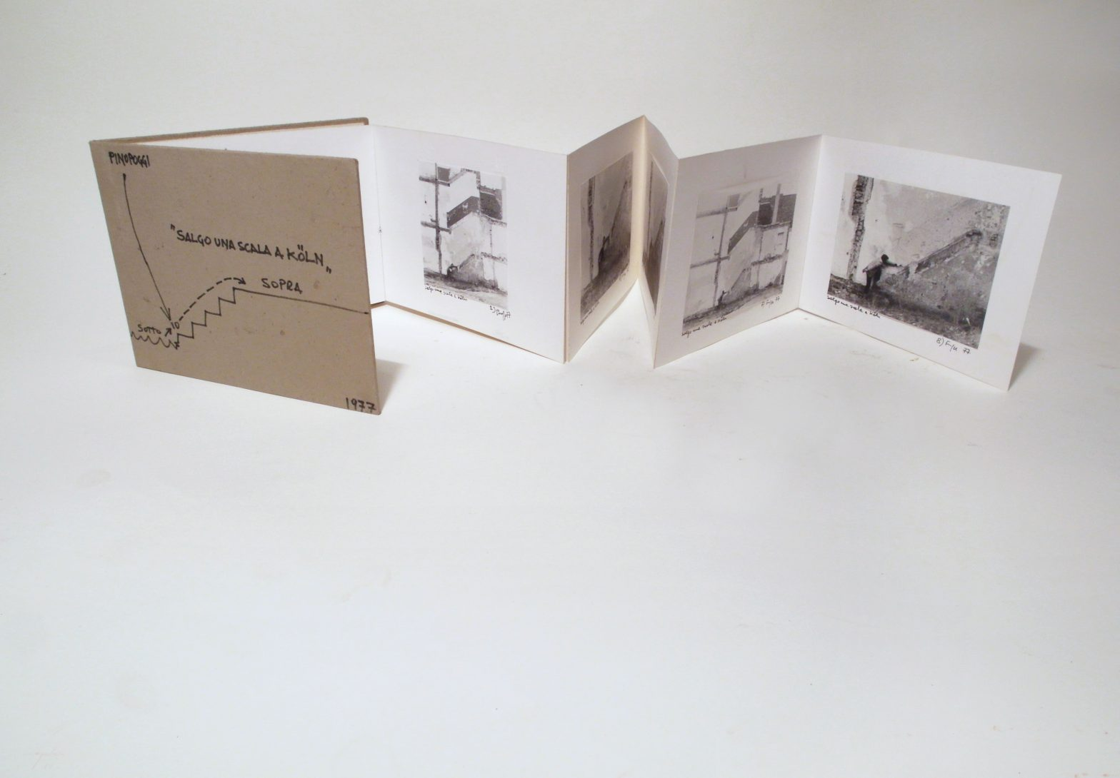 Opened fanfolded book. Each page shows a photograph a man in front of a wall. Visible traces of an stairway of torn down building on the wall.