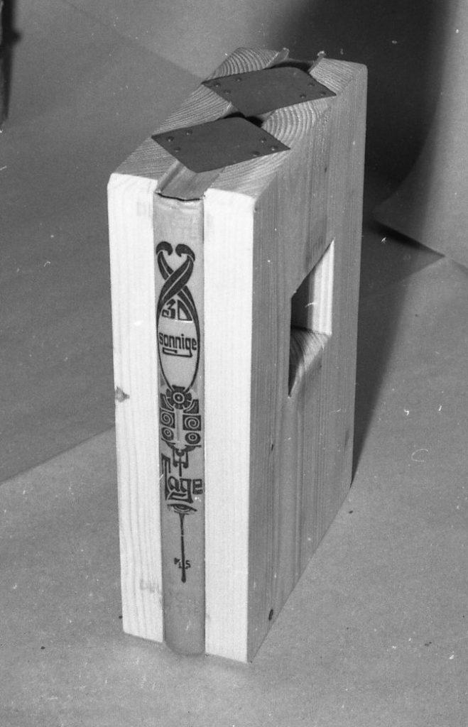 Book spine in between 2 wooden boards.